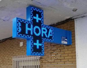 Pantalla electrónica sobre cruza de farmacia, iluminación led azul