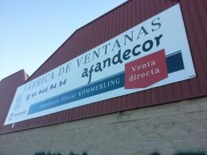 Valla publicitaria sobre fachada de nave industrial