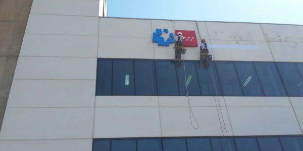 Momento del montaje sobre el muro de los logos luminosos de la Comunidad de Mdrid y el servicio de salud